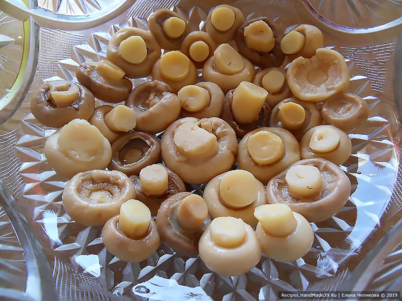 Салат укладывается в глубокую салатницу слоями. 1-й (нижний) слой – маринованные грибы (шампиньоны или другие), выложенные шляпками вниз