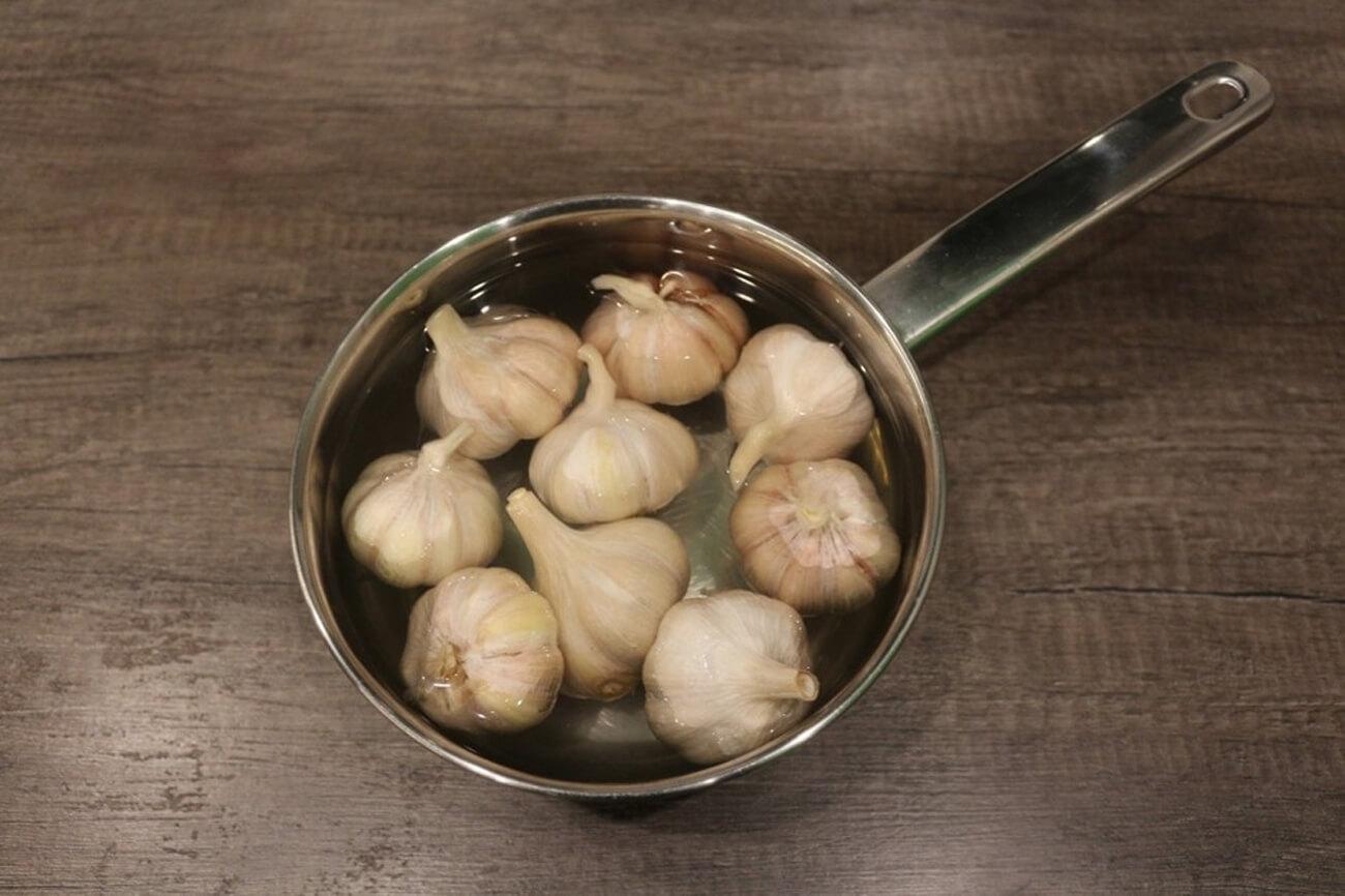 Отдельно вскипятить воду, влить крутой кипяток в чеснок, бланшировать головки примерно три-четыре минуты. После откинуть головки чеснока на сито
