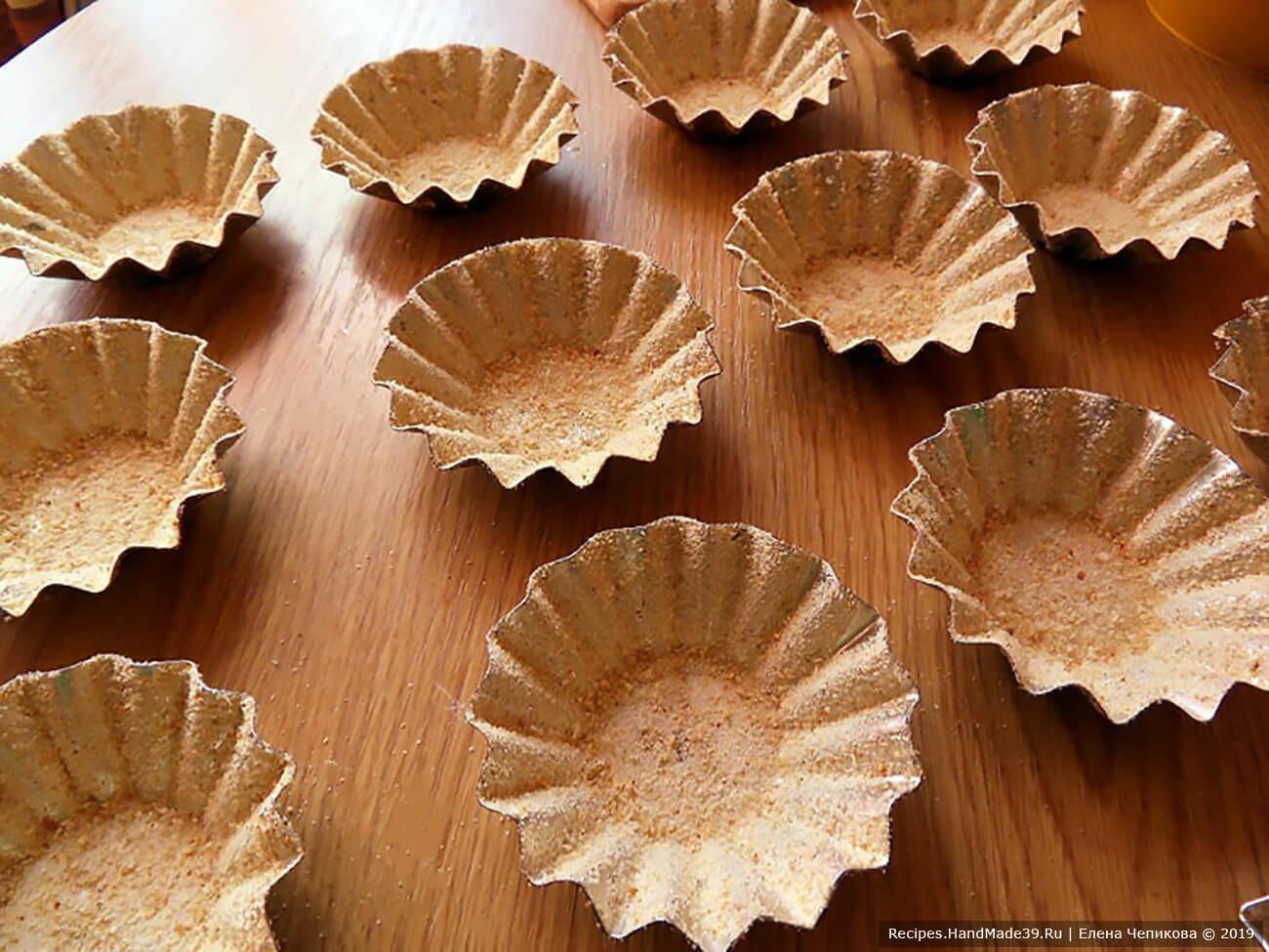 Формочки для кексов смазать растительным маслом, затем обсыпать панировочными сухарями, распределяя их не только по дну, но и по стенкам формочек