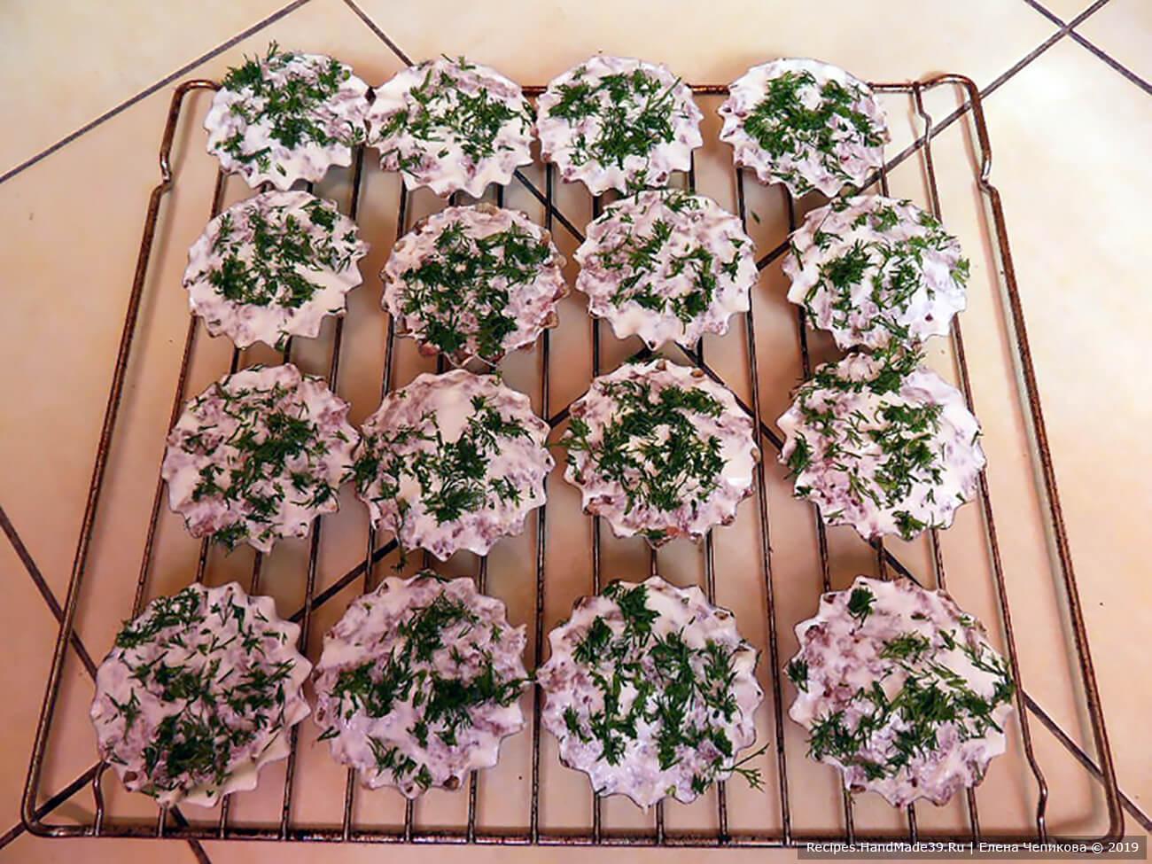 Обильно смазать верх каждого кекса сметаной, посыпать рубленой зеленью