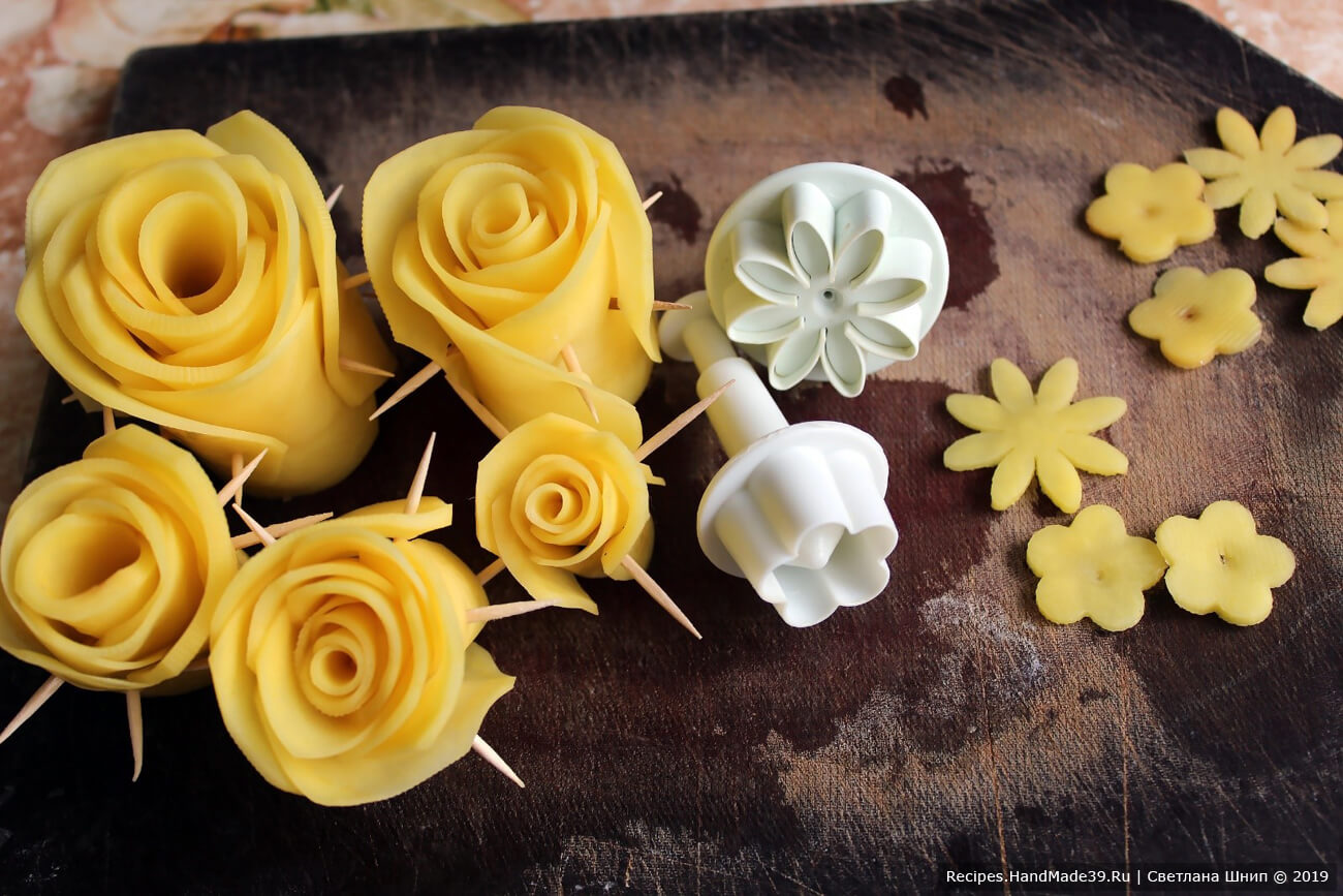Очищенный картофель нарезать тонкими пластинами. Скрутить из пластин «розы», закрепляя конструкцию зубочистками