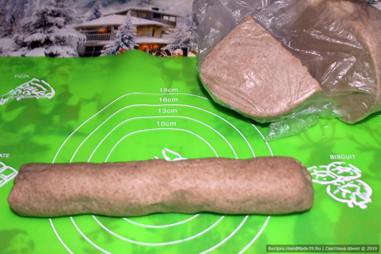Выложить тесто на посыпанную мукой поверхность, разделить на 2 части. Одну часть обернуть пищевой плёнкой, из второй части скатать «колбаску»