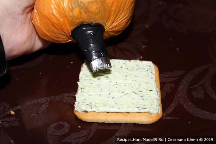 Крекер или ломтик белого хлеба густо намазать творожной массой