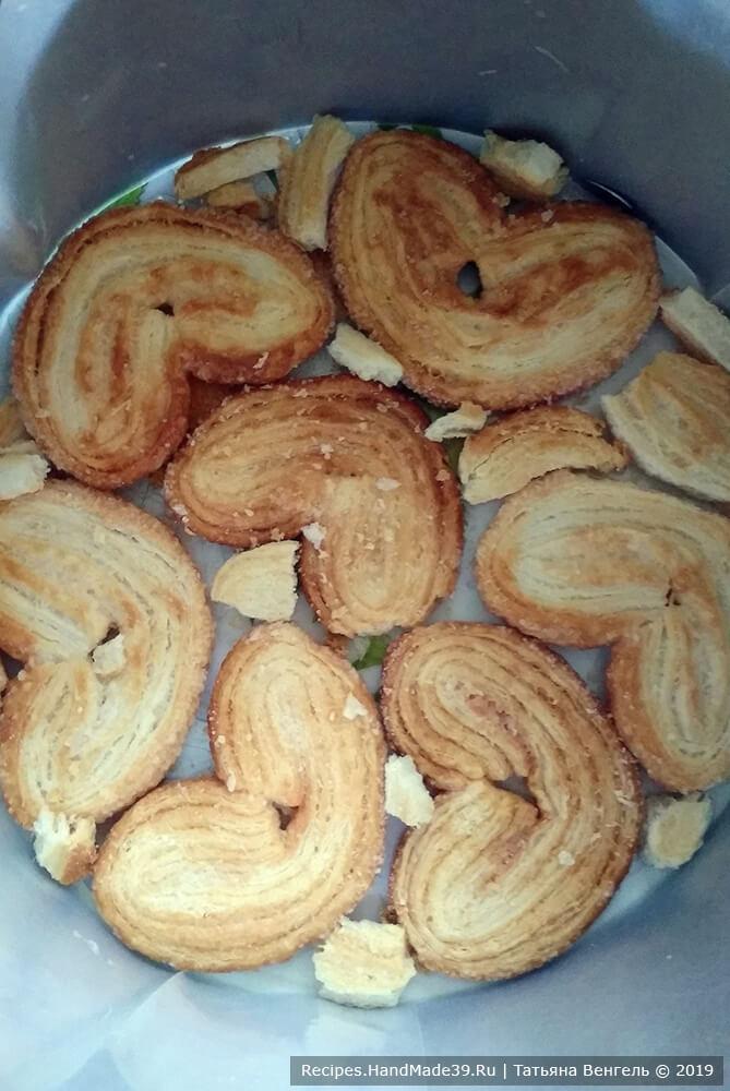 Разъёмную форму Ø 20 см установить на блюдо, бока формы выстелить плёнкой, на дно уложить слой печенья «Ушки»