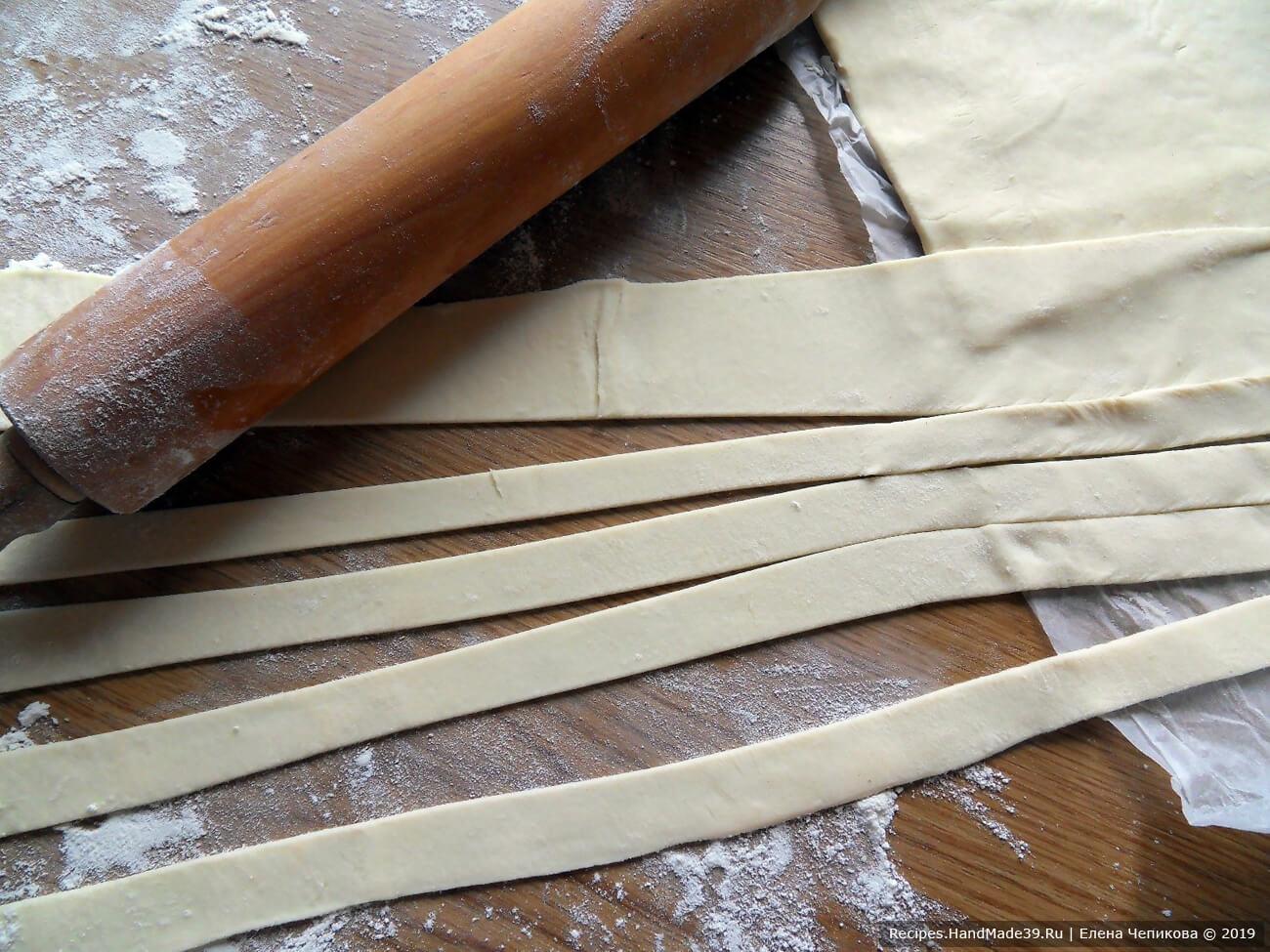 Слоёное бездрожжевое тесто разморозить, раскатать. Разрезать тесто на полоски шириной 1 см