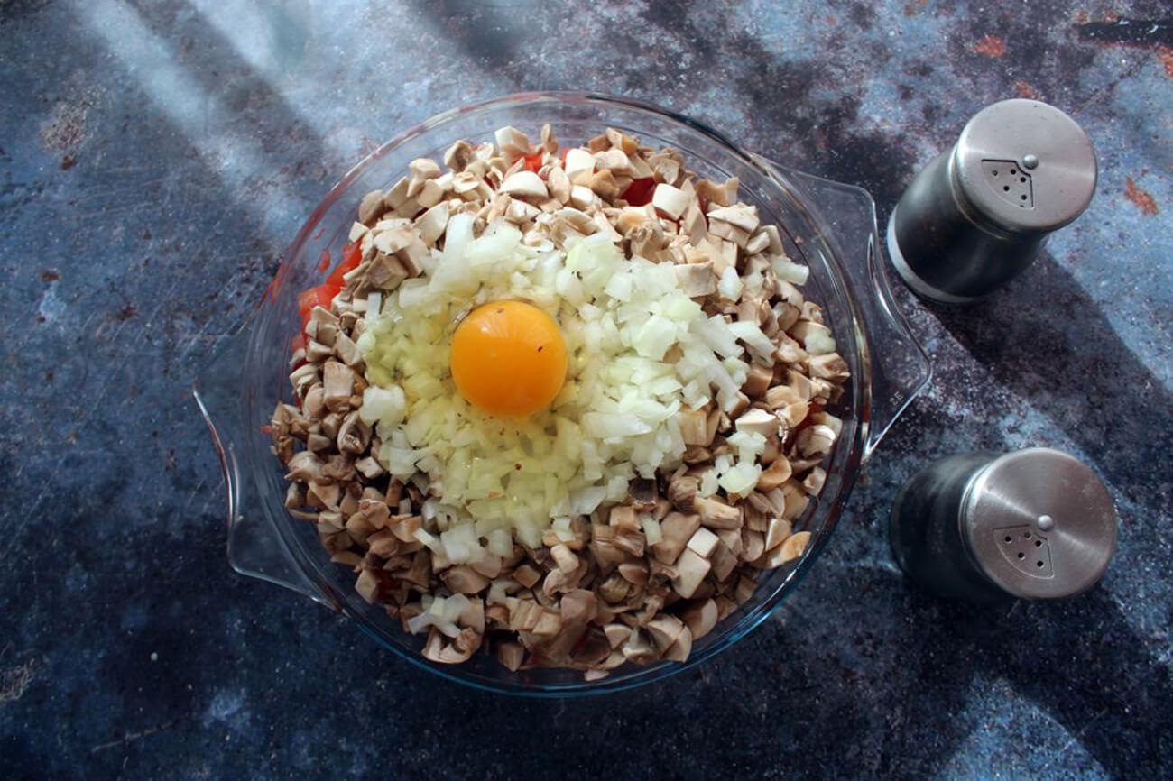 В миску выложить фарш, добавить нарезанные лук, шампиньоны и помидоры, вбить яйцо, поперчить, посолить и перемешать