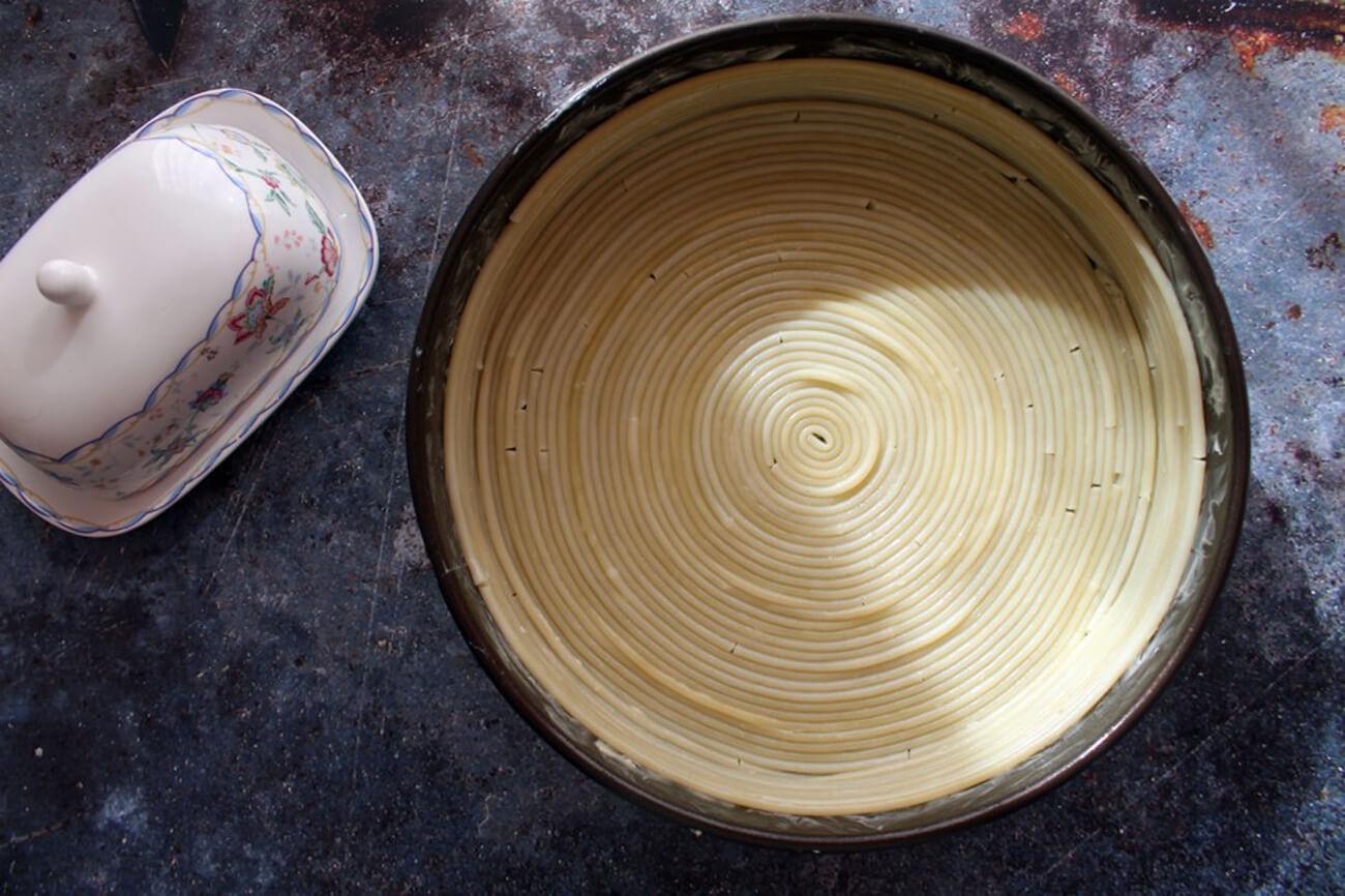 Круглую форму для выпечки обильно смазать сливочным маслом, и, начиная с центра, выложить букатини спиралькой на дно, а затем и по бокам