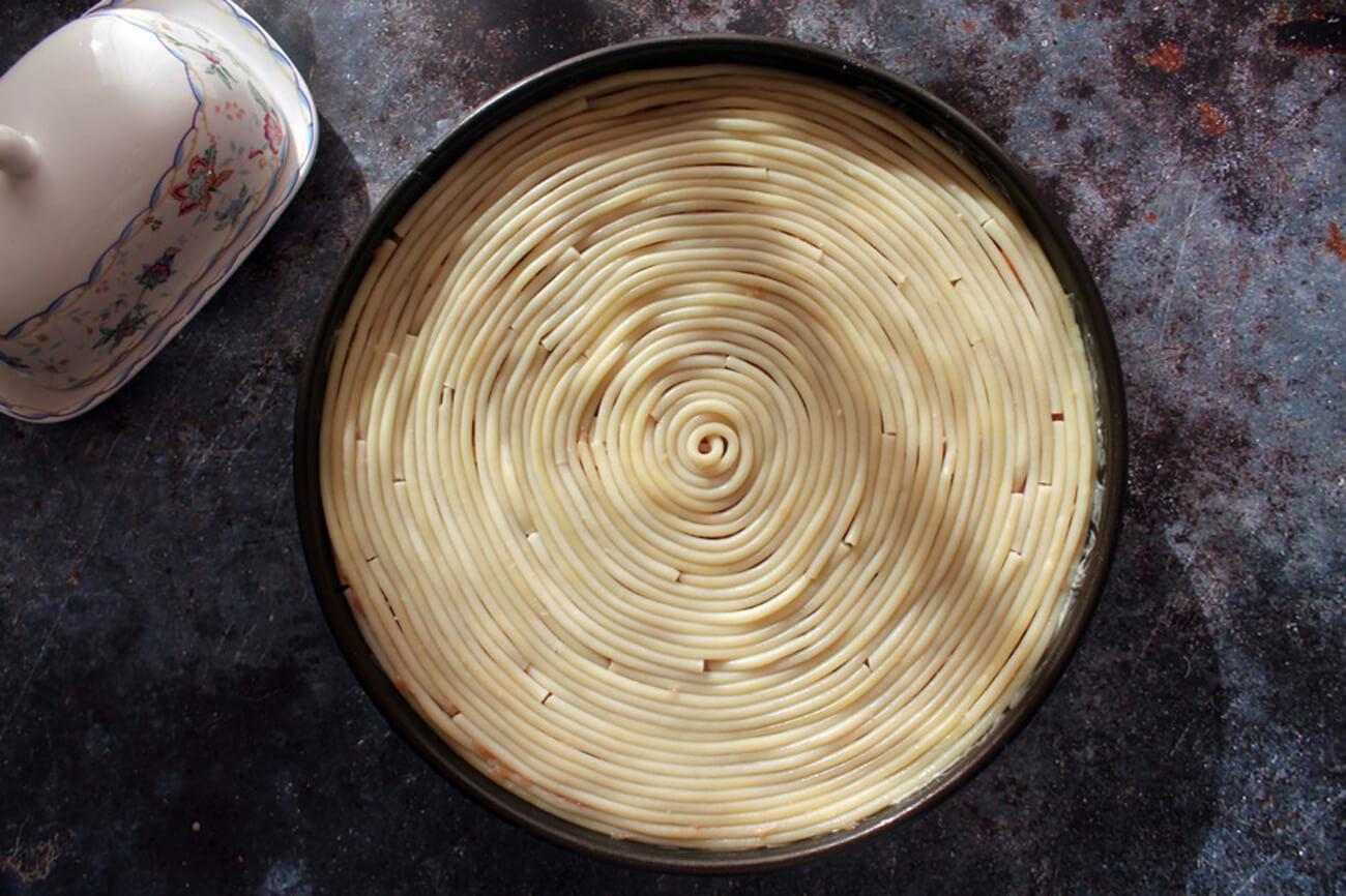 Мясную начинку так же закрыть выложенными спиралью букатини. Тимбаль сверху накрыть пекарской бумагой, смазанной маслом