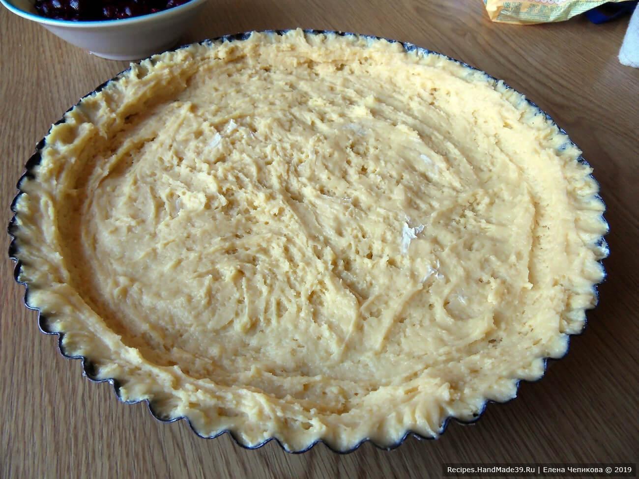 Форму для выпекания смазать маслом или маргарином. Выложить готовое тесто, руками распределить по дну и сделать бортики