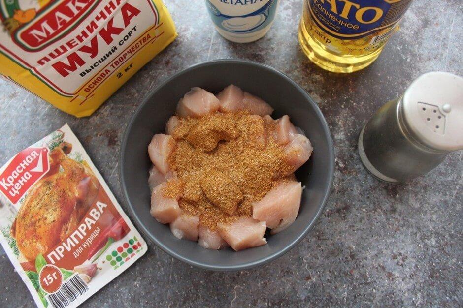 Переложить нарезанные кусочки филе в миску, добавить 1 ст. л. приправы для курицы, перемешать, накрыть миску пищевой плёнкой и поставить в холодильник мариноваться на 1 час