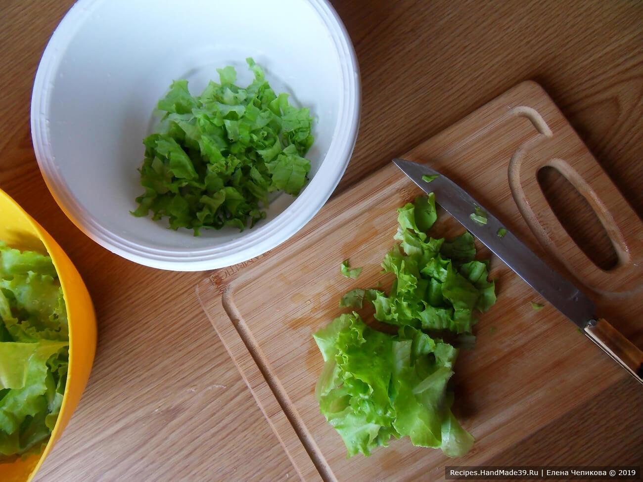 Зелёный салат (или пекинскую капусту) вымыть, стряхнуть воду. Нарезать полосками
