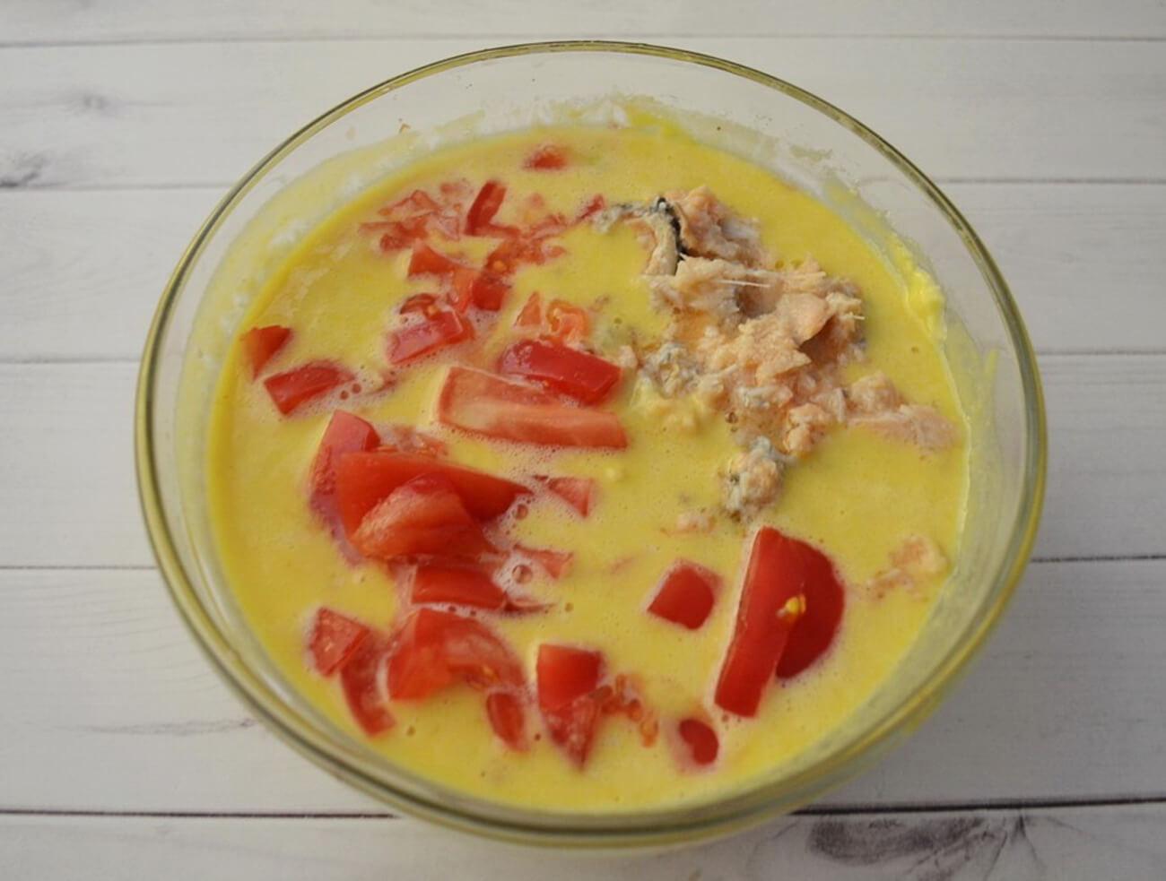 Рыбные консервы слить, рыбу размять вилкой. Добавить в тесто размятую рыбу и порезанный помидор