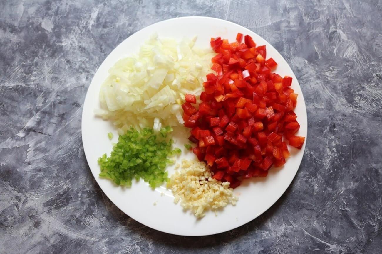 Очистить овощи. Лук и сладкий болгарский перец нарезать маленькими кубиками. Перец чили и чеснок мелко порубить