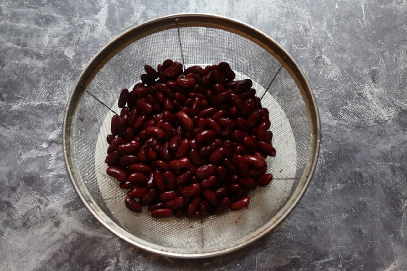 Красную консервированную фасоль промыть холодной водой, после чего откинуть на дуршлаг