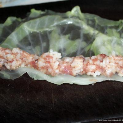 Выложить начинку из фарша вдоль половинки листа со стороны отрезанной толстой части