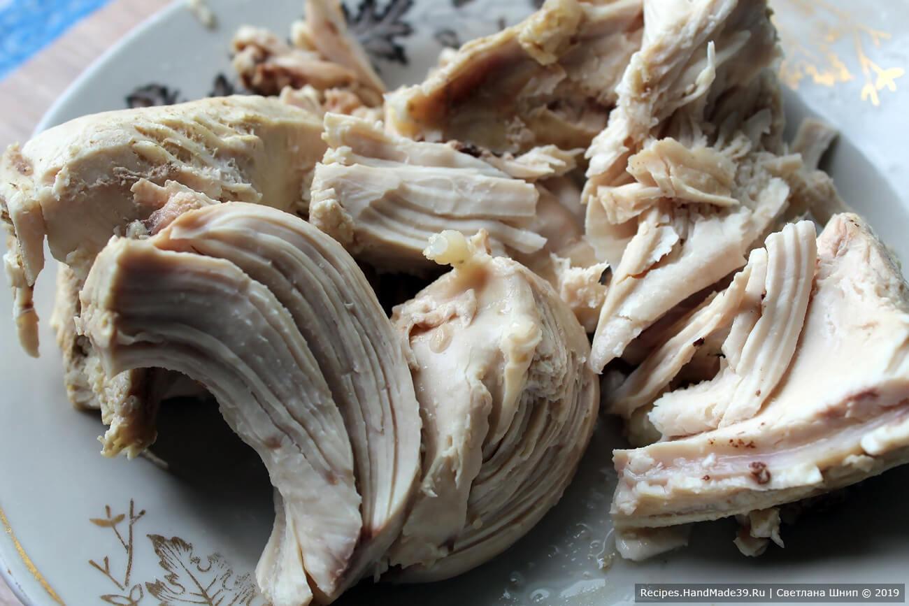 Достать из бульона мясо, отделить от костей, нарезать кусочками, опустить обратно в бульон