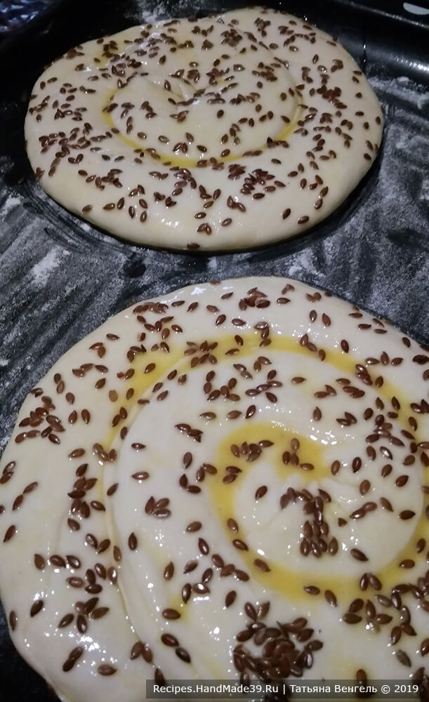 Выложить «улитку» на противень, слегка присыпанный мукой, смазать взбитым яйцом, посыпать семенами льна (или кунжута)