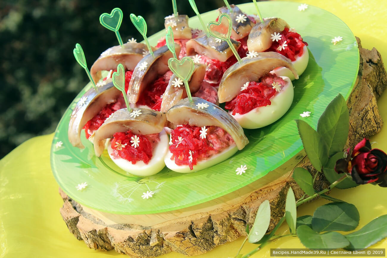 Сверху выложить сельдь (по 1 кусочку на каждую половинку яйца). По желанию украсить зеленью, и наша закуска – фаршированные яйца «Ленивая селёдка под шубой» – готова, приятного аппетита!