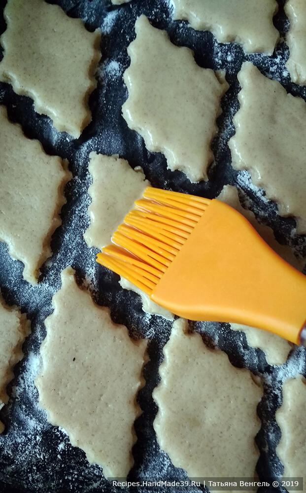 Раскатать тесто в пласт толщиной 0,5-0,7 см. Вырезать печенье, уложить на противень, смазать поверхность печенья яйцом