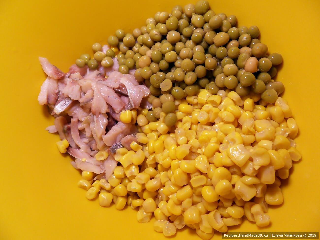 Филе солёной сельди нарезать тонкими полосками. Соединить с консервированным зелёным горошком, консервированной кукурузой