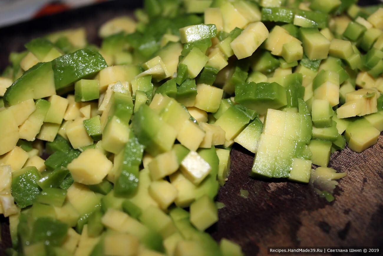 Приготовление салата из авокадо: авокадо разделить на 2 половинки, почистить, мелко нарезать, сбрызнуть соком лимона