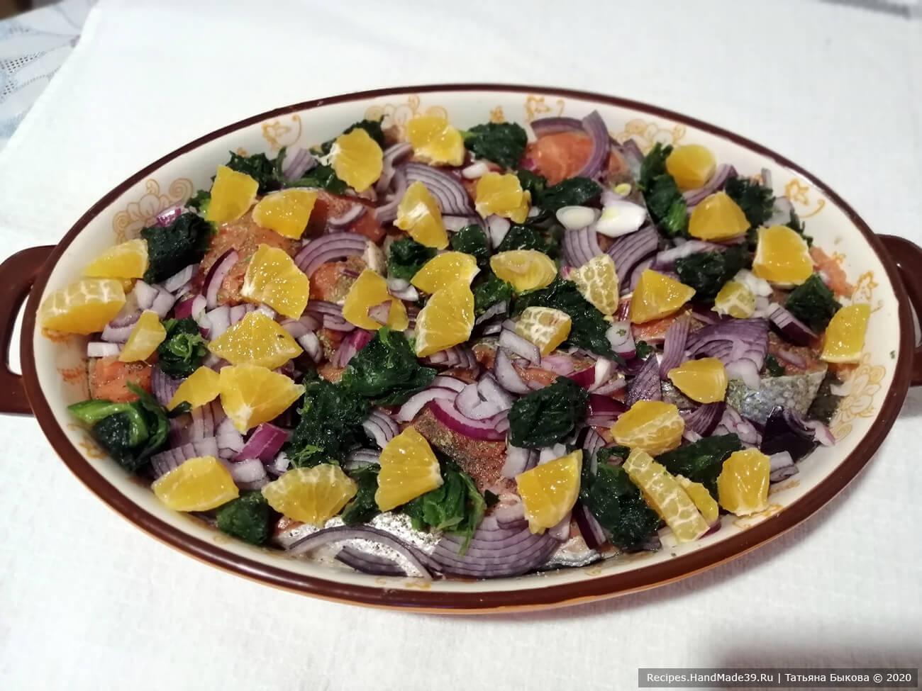 Выложить лук, мандарины и шпинат сверху рыбы. Залить подготовленную рыбу соусом