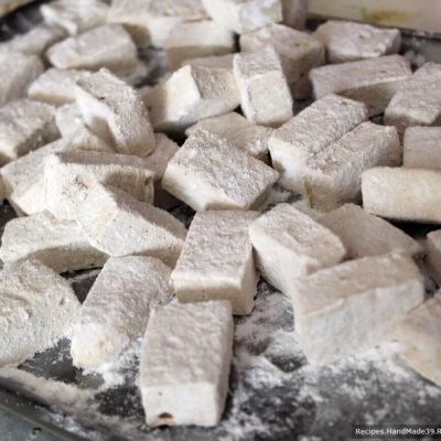 Нарезать маршмеллоу на кубики ножом, смоченным в воде (или смазанным растительным маслом), обвалять в смеси кукурузного крахмала и сахарной пудры