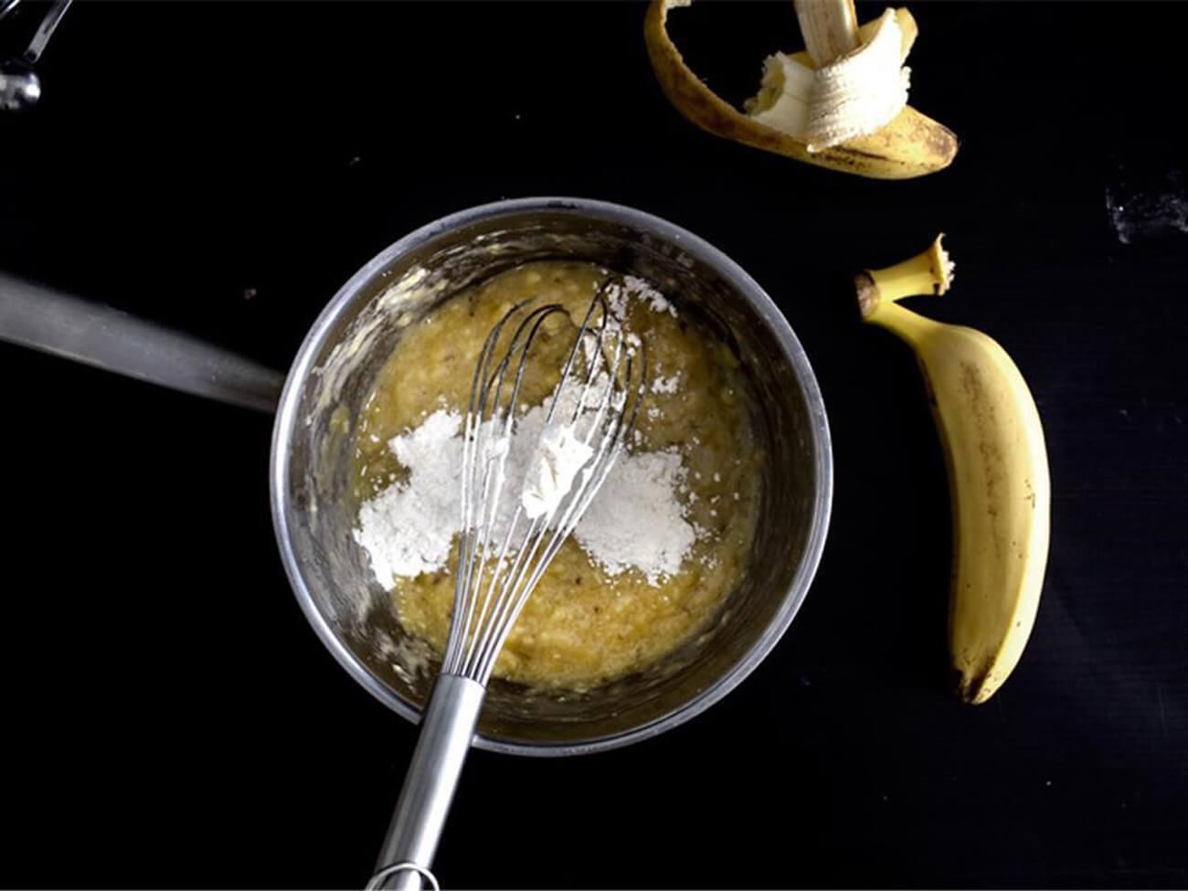 Соединить очищенные бананы и сахар в кастрюле, размять бананы настолько, насколько это возможно сделать венчиком. Добавить муку и хорошо перемешать