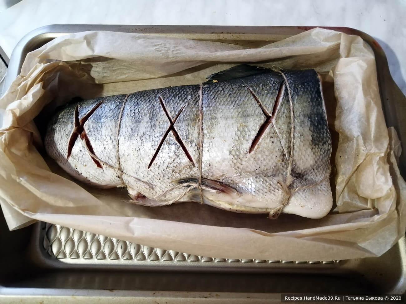 Перенесите пергамент с рыбой на противень и поставьте на 30 минут в духовку, разогретую до температуры 220 °C