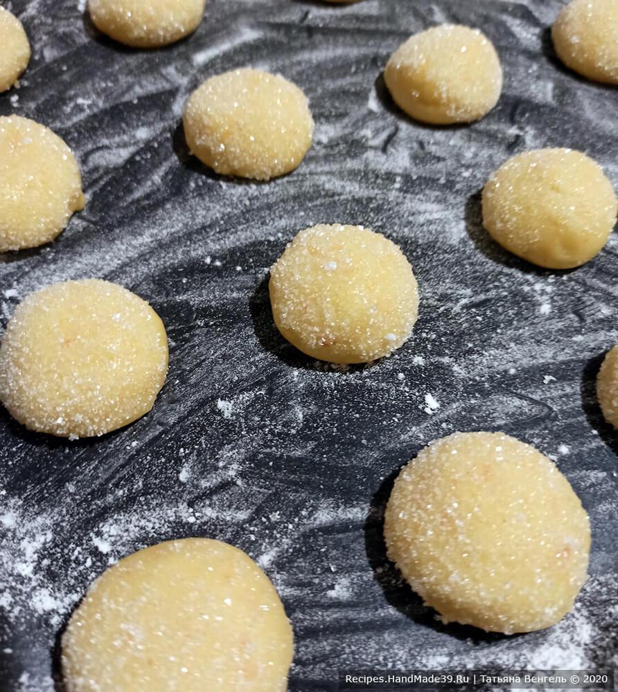 Скатать небольшие шарики размером чуть меньше грецкого ореха. Обмакнуть верх печенья в сахар, уложить на противень