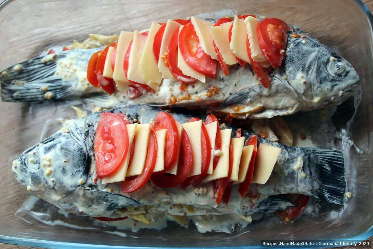 В надрезы рыбы вставить ломтики помидора и сыра, чередуя их