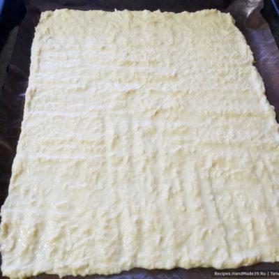 На противень застелить пергаментную или силиконизированную бумагу, выложить тесто тонким ровным слоем примерно 30 см × 35 см