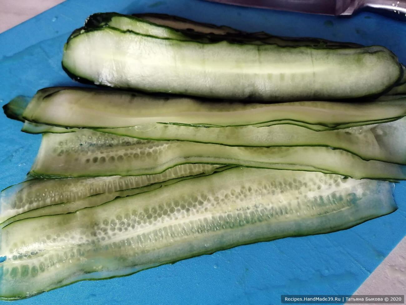 Огурцы вымыть, с помощью овощечистки нарезать по длине на полоски