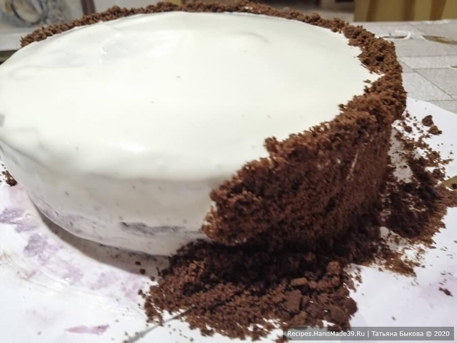 Шоколадный торт «Вишнёвый каприз» – фото шаг 12. Накрыть третьим коржом, обмазать весь торт оставшимся кремом, выровнять его. Под торт положить бумагу, чтобы блюдо после обсыпки осталось чистым.  Бока обсыпать крошкой