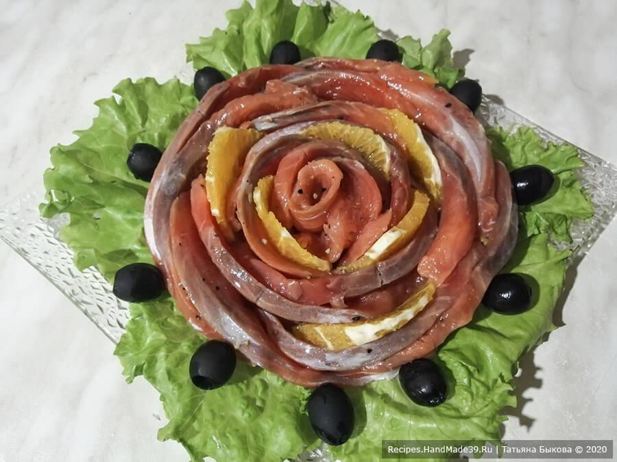 Слабосолёный лосось с апельсином – фото шаг 5. Для подачи свернуть из ломтиков «розочку», в некоторых местах переложив рыбу пластинами апельсина. «Розочку» выложить на листья зелёного салата, украсить маслинами. Приятного аппетита!