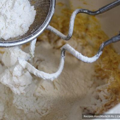 Печенье «Мандариновые дольки» – фото шаг 4. Порциями добавить муку, просеянную через сито